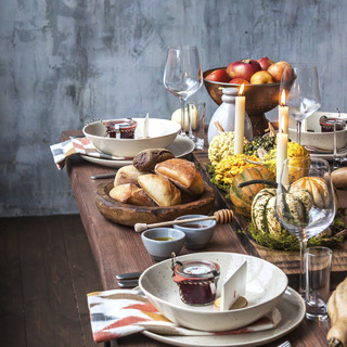 Rustic table setting with pumpkin soup and pumpkins on the background of the window in the loft