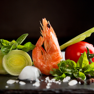 Shrimp prawn serving with leek, basil, ice against black background. Seefood diet concept. Healthy food