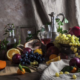 Still life with red wine, fruits, pomegranate, grapes and cheese.