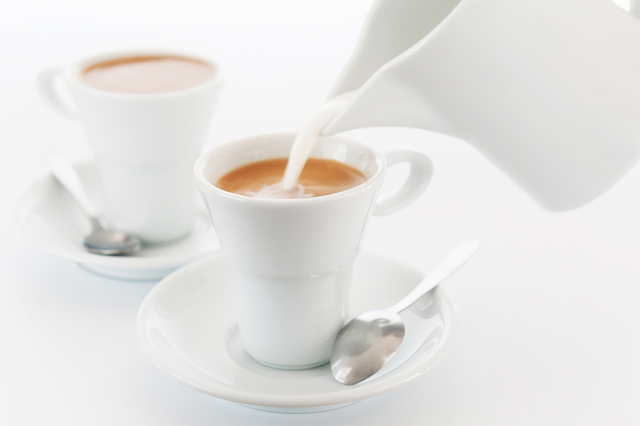Milk is poured into a cup of coffee. White cups and a milkman on a white background. A large plan. An elective focus.